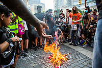 NEW YORK, NY - JULY 4: A man throws a flag into fire during during a Black Lives Matter protest at Columbus Circle in New York, NY on July 4, 2020. Protests continue in New York and all movements and actions take place in the context of protests against the murder of George Floyd and other African Americans by the police in the United States. (Photo by Pablo Monsalve / VIEWpress via Getty Images)
