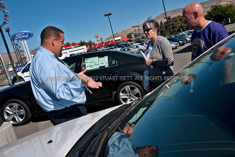 9/26/2009--Wenatchee, WA, USA..Michelle Burchett, along with her husband Jeff (right) and their daughter Isobel, visiting Town Ford in Wentachee, WASH., where she hoped to buy a Ford Fusion with the help of salesman Chad Lee (left).  The Burchett'sgot$1500 cash back and the lowest APR available on the car....©2009 Stuart Isett. All rights reserved.