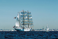 A three masted Barque ships at full sail set among the sailboats and yachts filling New Yorks harbor for the Statue of Liberty's bicentenial celebration. Boats, spectator events, nautical, sailing. New York.