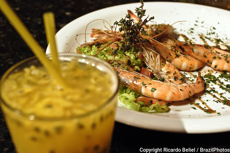 Brazilian cuisine, Camarão à Paulista ( Shrimp a Paulista mode ), served with batida de maracujá ( passion-fruit batida ) at Mangue Seco restaurant at Lapa district in Rio de Janeiro, Brazil. Batida is a brazilian drink made of cachaça, a fruit, sugar and ice.