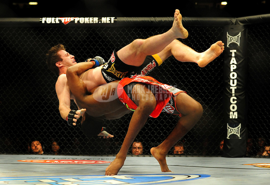 Jan. 31, 2009; Las Vegas, NV, USA; UFC fighter Stephan Bonnar (black trunks) is lifted off the mat by Jon Jones (red trunks) during the light heavyweight swing bout in UFC 94 at the MGM Grand Hotel and Casino. Mandatory Credit: Mark J. Rebilas-