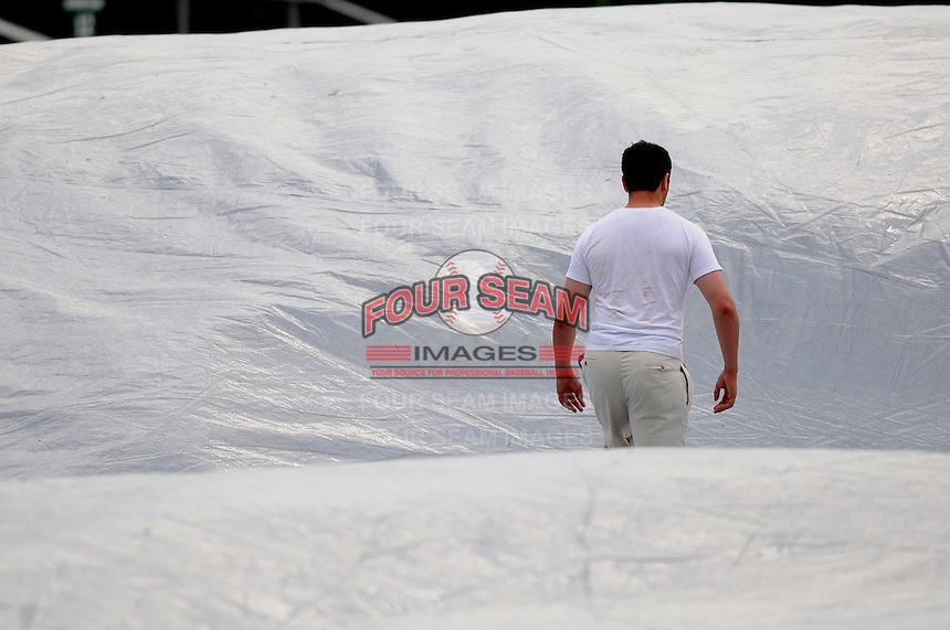 Grounds crew members of the Potomac Nationals pull the tarp during a rain delay prior to a game against the Salem Red Sox on June 16, 2011, at Pfitzner Stadium in Woodbridge, Va. Photo by Tom Priddy / Four Seam Images