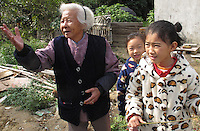 20120117 CHINA GUANGDONG PROVINCE : An old woman and her grandchildren are seen in a small village next to Hallstatt, China's copy of the Austrian alpine town of the same name, Boluo Township, Huizhou City, Guangdong Province, China, 17 January 2012. Property developments such as this are expected to run into financial difficulites in 2012 as the Chinese economy and property market continue to cool, in reaction to the ongoing sovereign debt crisis in Europe.<br /> SINOPIX / ALEX HOFFORD
