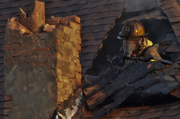 Buffalo Rescue 1 Captain Mark Eghoff pokes his head through the roof of a structure on Grant Street. One civilian was rescued during this fire by Buffalo Police.