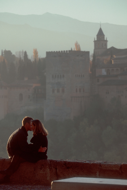 Spain, Grenada, Young couple oblivious to the Moorish architecture of the Alhambra and the Sierra Nevada in the distance, Andalucia, Spain..