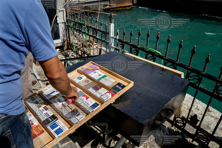 A customer picks a packet of Winstons from a pavement cigarette vendor in Karakoy.