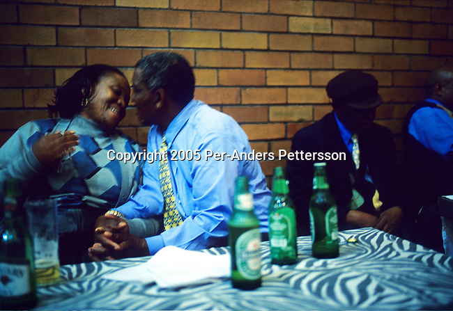 SOWETO, SOUTH AFRICA APRIL 23: An unidentified couple socialize during a late night session at a Jazz club on April 23, 2005 in Diepkloof Hall in Soweto, Johannesburg, South Africa. The club has monthly sessions where people come to enjoy classic jazz music, eat and have a few drinks. People are encouraged to perform dance numbers to their favorite tunes. The Soweto is South Africa?s largest township and it was founded about one hundred years to make housing available for black people south west of downtown Johannesburg. The estimated population is between 2-3 million. Many key events during the Apartheid struggle unfolded here, and the most known is the student uprisings in June 1976, where thousands of students took to the streets to protest after being forced to study the Afrikaans language at school. Soweto today is a mix of old housing and newly constructed townhouses. A new hungry black middle-class is growing steadily. Most residents work in Johannesburg but the last years many shopping malls has been built, and people are starting to spend their money in Soweto. .(Photo by Per-Anders Pettersson/Getty Images).