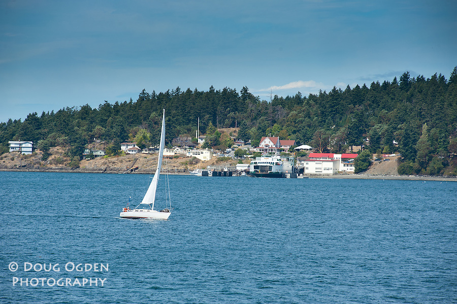 A sailboat glides past the ferry landing at Orcas Island, San Juan Islands, Washington