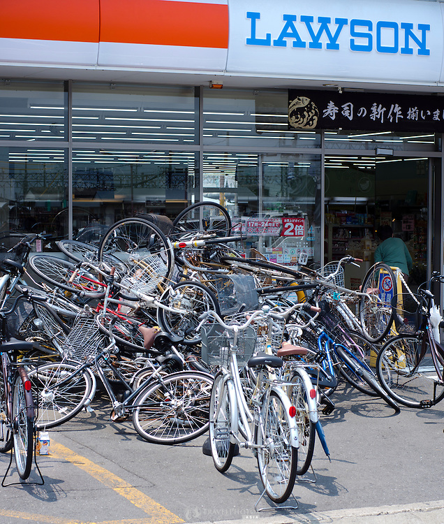 A pile of abandoned bicycles in front of a convenience store in Japan.