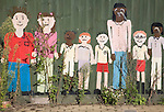 Painted collage picture of young children on a nursery school fence, Wickham Market, Suffolk, England