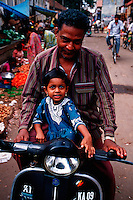 Portrait of a smiling young Indian girl as she rides on a moped with her proud father along the open air market lining the street. India.