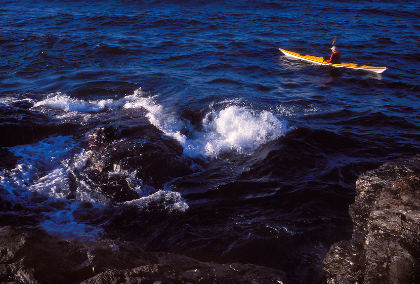 A KAYAKER PADDLES LAKE SUPERIOR OFF THE COAST OF PRESQUE ISLE PARK IN MARQUETTE MICHIGAN.