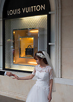 Holding hands for the Photographer outside the modern Louis Vuitton shop, a popular area for wedding photography in Hanoi. That is everyday life in the streets of Hanoi, Vietnam