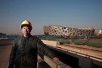 A migrant worker who has been working as manual labor on various projects at the National Stadium AKA the Bird's Nest for the past two years, is photographed near the stadium in Beijing, China..