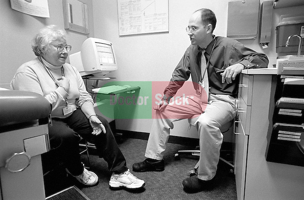 Elderly female patient discussing symptoms with young male doctor in examination room