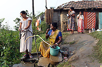 Residents of the Captain Bherry community in Kolkata gather around a water pipe in the early morning. Poverty is still rife in the city and access to plumbing remains a privilege for for the few. India. November, 2013