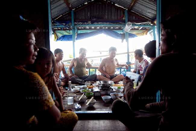 "Neighbors gather for lunch on their boat house on the Hau Giang River, a tributary of the Mekong River, in Chau Doc, in the An Giang Province, Vietnam. Most of the family members are fishermen and have lived on the river for most of their lives. When the Mekong River reaches Vietnam it splits into two smaller riveres. The ""Tien Giang"", which means ""upper river"" and the ""Hau Giang"", which means ""lower river"". Photo taken on Monday, December 7, 2009. Kevin German / Luceo Images"