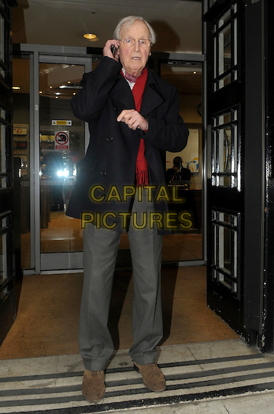 Nicholas Parsons leaving the studios of BBC Radio 2, London, England..January 18th, 2012.full length black jacket red top grey gray trousers glasses talking on mobile phone .CAP/IA.©Ian Allis/Capital Pictures.