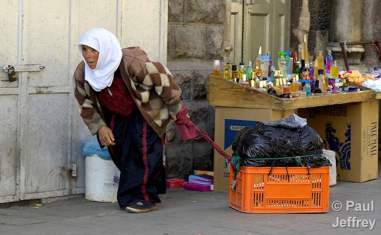 A Palestinian woman pulls a box on a Jerusalem street.