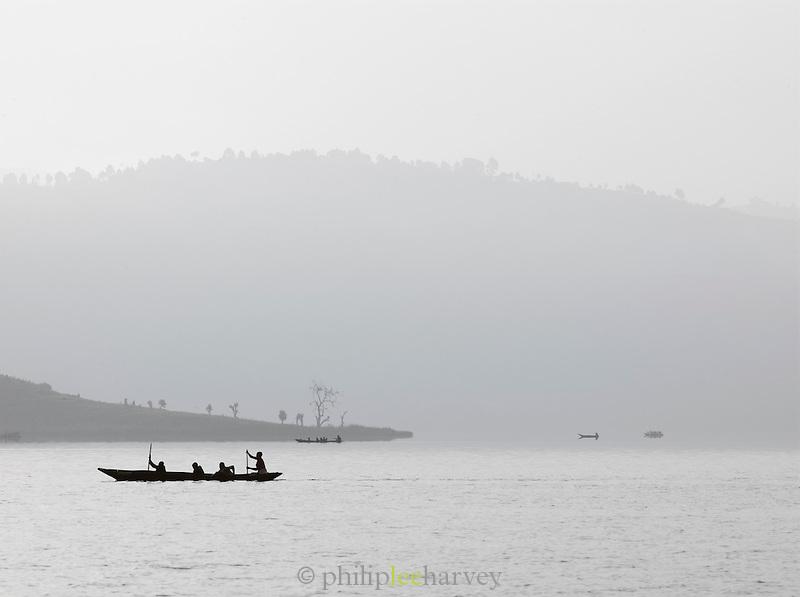 Small local wooden boats travelling across calm waters of Lake Bunyonyi, South Western Uganda