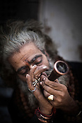 A sadhu smokes ganja outside the Pashupathi Nath Temple in capital Kathmandu, Nepal