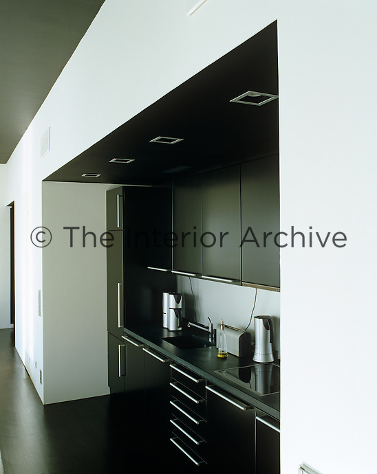 A black contemporary kitchen is built into a recess in the wall of this loft conversion