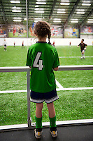 Young soccer player watches an indoor game.