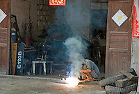 Man brazing under a cloud of smoke at the door of his garage, Yangshuo, Guangxi, China.