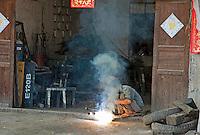 Man brazing under a cloud of smoke at the door of his garage, Yangshuo, Guangxi, China.
