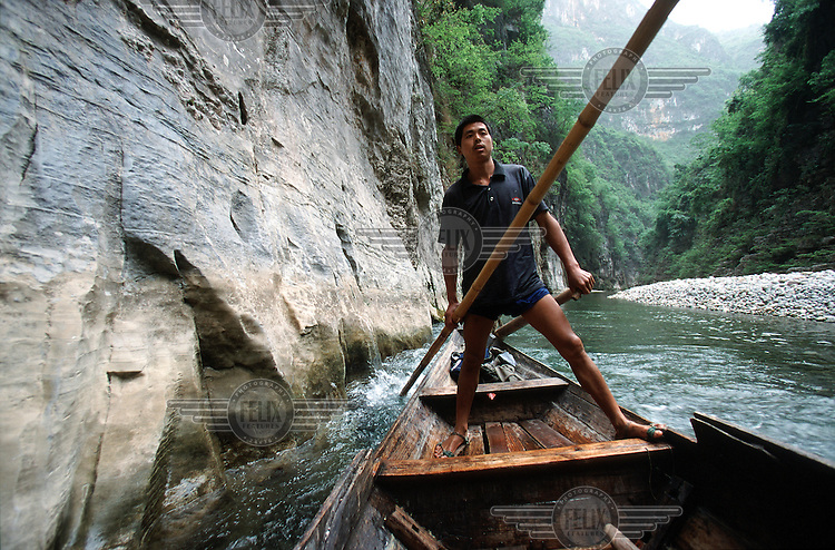 A tracker steers a small boat down stream in the Mini 3 Gorges near Wushan. Once a common sight along the treacherous waterways of the Yangtze river, trackers are a rare sight tooday. The gorges will be flooded by the Three Gorges dam project.