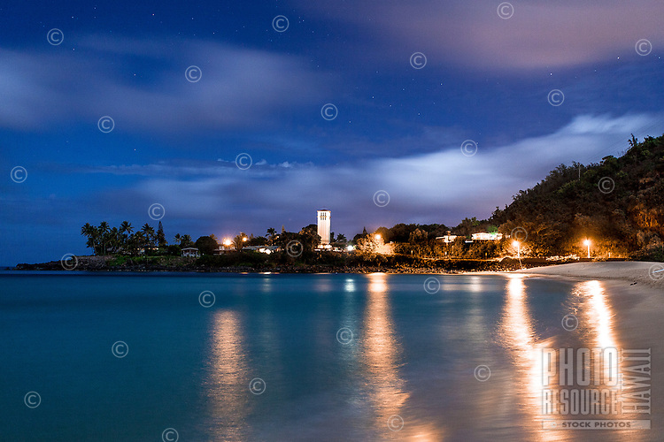 Waimea Bay at night with lights reflecting off the water, North Shore, O'ahu.