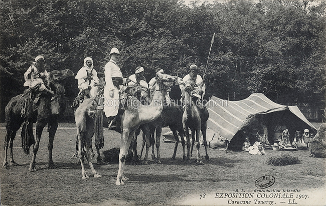 Tuareg caravan, with Berber Saharan Africans and a Frenchman on Mehari dromedaries, at the Colonial Exhibition of 1907, held in the Jardin d'Agronomie Tropicale, or Garden of Tropical Agronomy, in the Bois de Vincennes in the 12th arrondissement of Paris, postcard from the nearby Musee de Nogent sur Marne, France. The garden was first established in 1899 to conduct agronomical experiments on plants of French colonies. In 1907 it was the site of the Colonial Exhibition and many pavilions were built or relocated here. The garden has since become neglected and many structures overgrown, damaged or destroyed, with most of the tropical vegetation disappeared. The site is listed as a historic monument. Picture by Manuel Cohen / Musee de Nogent sur Marne