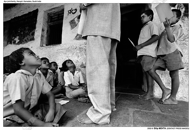 At a primary school owned by the Ajur family, children sit on the ground and listen to their teacher. The school is for children from other families as well. In the photograph some of the children are from the Ajur family.