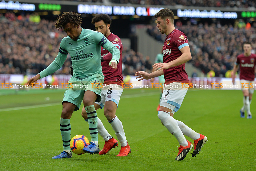 Alex Iwobi of Arsenal is tackled by Aaron Cresswell of West Ham United and Felipe Anderson during West Ham United vs Arsenal, Premier League Football at The London Stadium on 12th January 2019