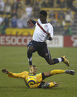 USA's Eddie Johnson jumps over a sliding Tyrone Marshall in the first half during a 1-1 tie with Jamaica in the semifinal round of CONCACAF Qualifying for the 2006 FIFA World Cup, in Columbus, Ohio, Wednesday, Nov. 17, 2004.