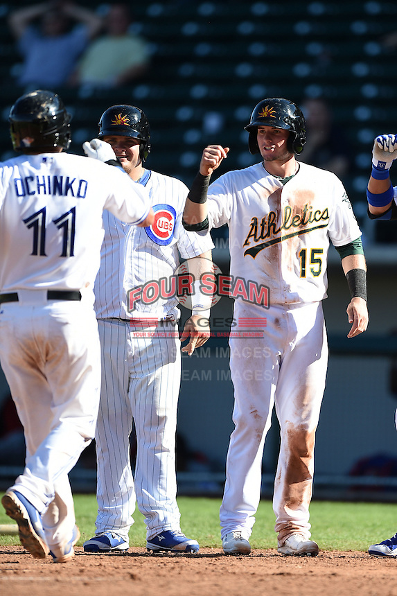 Mesa Solar Sox catcher Sean Ochinko (11) is greeted at home by Dan Vogelbach (22) and Daniel Robertson (15) after hitting a home run during an Arizona Fall League game against the Surprise Saguaros on October 17, 2014 at Cubs Park in Mesa, Arizona.  Mesa defeated Mesa 5-3.  (Mike Janes/Four Seam Images)