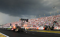 Aug. 31, 2013; Clermont, IN, USA: NHRA top fuel dragster driver Terry McMillen (near lane) races alongside Clay Millican under dark clouds of an approaching storm during qualifying for the US Nationals at Lucas Oil Raceway. Mandatory Credit: Mark J. Rebilas-