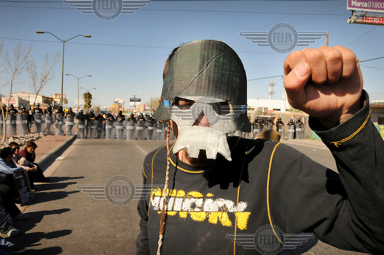 A demonstrator protests the visit of Mexican President Calderon to Cuidad Juarez. He wears a mask symbolising the army. Ciudad Juarez has become the world's most dangerous city. More than 2,600 people were killed in 2009. Since President Calderon declared war on the drugs cartels in 2006 and deployed thousands of troops, the violence has only increased.