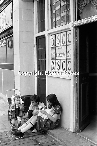 Children siblings brother and older sister look after family babies. Older girl playing with doll. They are waiting outside a Lunch Time Disco pub for their parents to re emerge. Elephant and Castle SE London 1970s UK ..