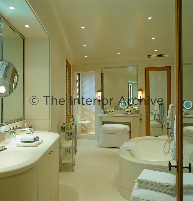 A glamorous contemporary bathroom incorporates a series of mirrors and mirrored doors into the design