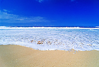 A wide expanse of frothy white sea foam kisses the warm tan sand on Oahu's North shore, home of the world's best surfing. In the distance, a brilliant blue sky meets the horizon of the mighty Pacific Ocean.