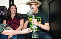 Emily Stevens (left) looks on as Reporter Harry Wallop (right) takes a bong marijuana hit during a Colorado Cannabis Tour in Denver, Colorado, Friday, September 30, 2016. <br /> <br /> Photo by Matt Nager