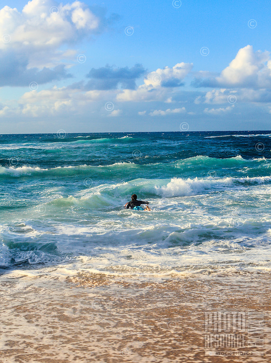 A surfer paddles out to sea  at Ho'okipa Beach, East Maui.