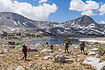 A group of backpackers descending toward L Lake in rugged terrain in the High Sierra mountains near French Canyon and Pine Creek Pass.