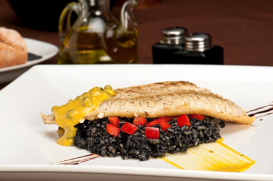 Plate of halibut fillet over a bed of rice with squid ink, capers tomato and mustard in a restaurant setting with copyspace.