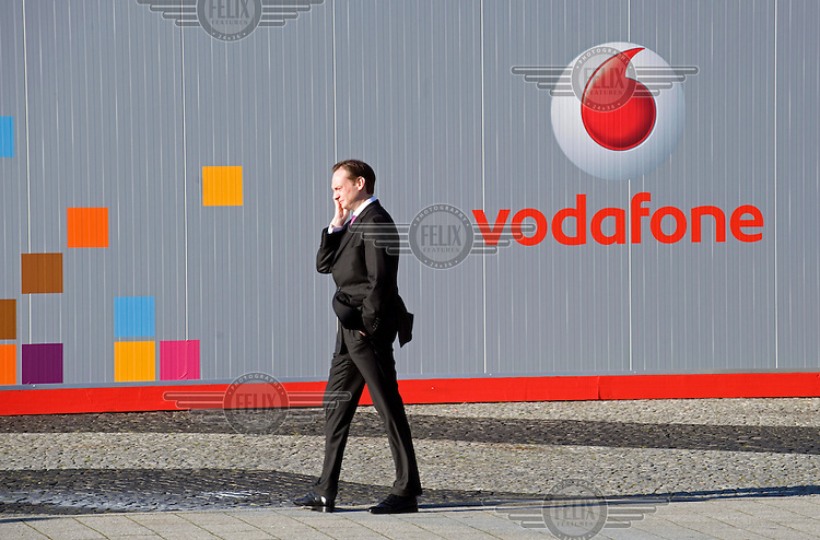 Visitor using his mobile phone at the Vodafone exhibit at the Computer Fair Cebit 2008 in Hanover.