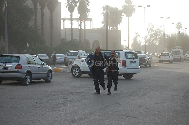 BAGHDAD, IRAQ:  Two men run from an explosion outside the Sheraton Hotel, January 25, 2010...At least 36 people have died in three large explosions apparently targeting hotels in the heart of Iraq's capital..More than 70 people were injured in the Baghdad blasts, which officials said were caused by suicide car bombers.  They struck near the Sheraton, Babylon and Hamra hotels, which are popular with Western businessmen and media....Photo by Qeas Kazm/Metrography