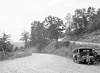A family stands next to their old-fashioned car on Indian Gap Road, Smokey Mountains, NC, in 1930's America.  (photo by bcpix.com)