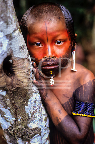 A-Ukre Village, Brazil. Young Kayapo boy with red urucum and black genipapo face paint and bead lip decoration. Ears and bottom lip pierced  Para State.
