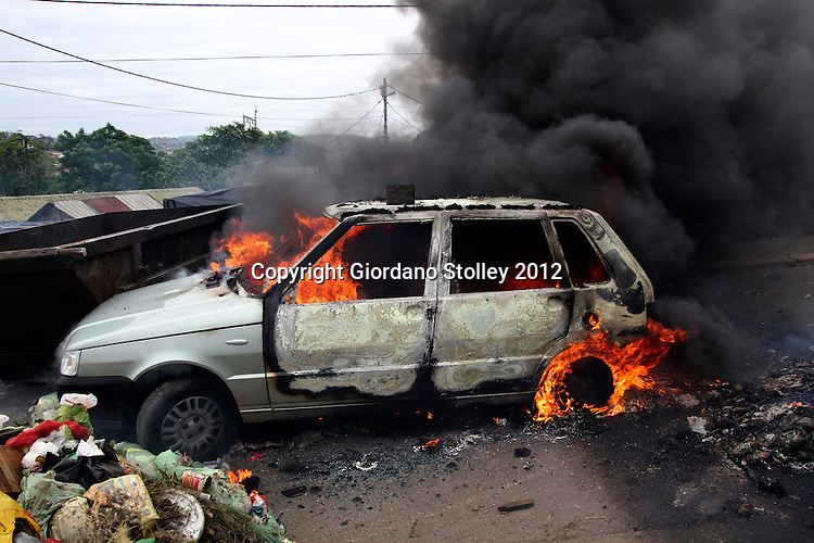 DURBAN - 25 November 2012 - The Brazilian made Fiat Uno of South African Press Association journalist Giordano Stolley burns in after being stoned and set alight in Durban's KwaMashu township bny supporters of the Inkatha Freedom Party. Their aim had been to use the car as a barricade to prevent rival National Freedom Party members from exiting the township's notorious A-section where a by-election was to be contested. Picture: Giordano Stolley/Allied Picture Press/APP